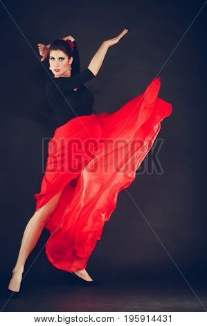 Culture in move. Beautiful talented girl making performance by oriental dance. Woman in action dancing in long flared red skirt on black background.