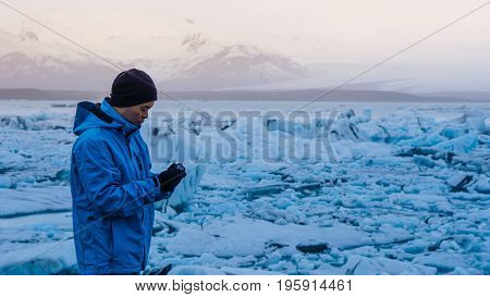 Asian Man Using Camera At Jokulsarlon, Glacier Lagoon Iceland. World Travel Destination