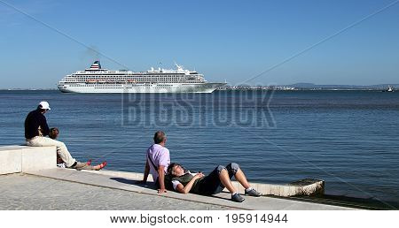 Lisbon, Portugal - April 27, 2014. People are resting near Tagus River in Lisbon, Portugal.