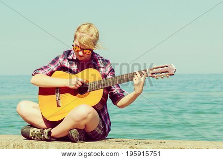 Music and people concept. Young woman traveller hiker with guitar outdoor on sea coast