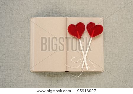 Two lollipops in the shape of a heart placed on an old diary with blank pages. Saint Valentine's Day, copy space.