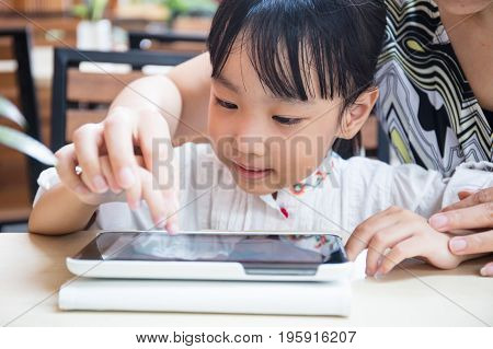 Asian Chinese Little Girl Playing Tablet Computer With Her Mother