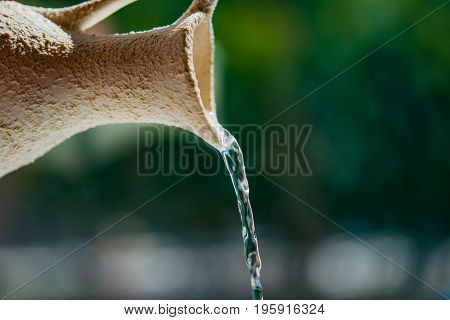 Abstract background. Water flows like a stream of light ceramic jug. The concept of ecology, the value of water