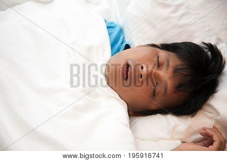 Asian man is snoring in bed and his have sleep apnea Health care concept.