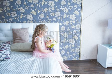 Little girl is sitting on the bed with a bouquet of peonies