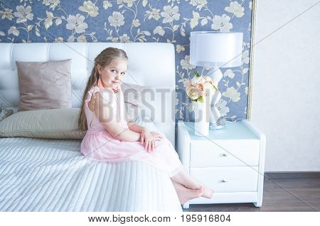 Little girl is sitting on the bed and looking at the camera
