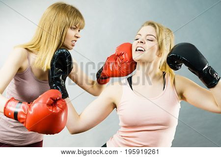 Two agressive women wearing boxing gloves having argue fight being mad at each other. Female violance concept.