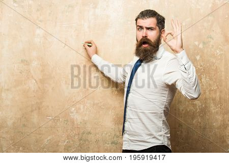 bearded man with long beard and hair on surprised face in tie and white shirt write on beige wall background with chalk and ok gesture copy space business and marketing education