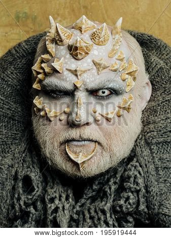 Demon head with grey collar on abstract beige wall. Alien or sorcerer makeup. Horror and fantasy concept. Man with dragon skin and beard. Monster face with white eyes sharp thorns and warts.