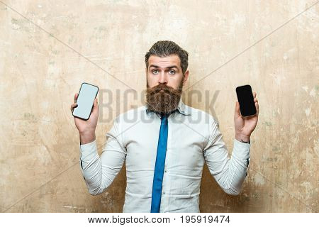 hipster or bearded man with long beard and stylish hair on surprised face in tie and white shirt on beige background compare mobile phone and smartphone conversation and information businessman