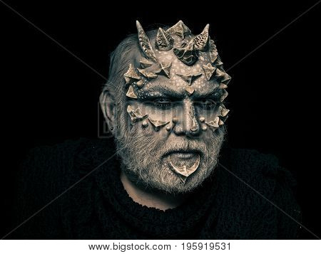 Man with dragon skin and beard. Demon head on black background. Monster face with white eyes sharp thorns and warts. Alien or reptilian makeup. Horror and fantasy concept.