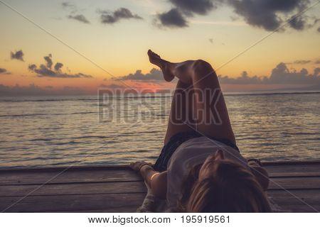 Girl enjoying the ocean tropical sunset / sunrise. Focus is on the feet.