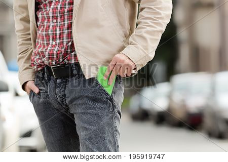 Man taking out / putting in cellphone from / into the pocket.