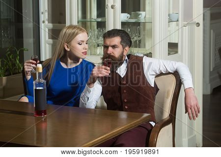 Girl And Man Sharing Bottle Of Red Wine In Restaurant