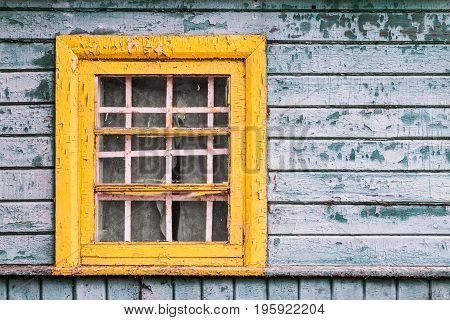 Yellow Window On Green Wooden Wall Of Abandoned House