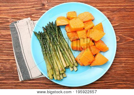 Baked asparagus pumpkin on plate on wooden background. Low fat healthy eating concept.