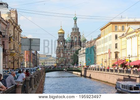 St. Petersburg, Russia - July 13 2017: Historic, picturesque griboyedov canal and street to Church on spilled blood full of pedestrians. Summer day, crowd of tourists. Water with the excursion boat