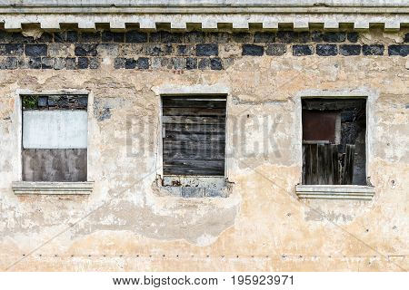 Boarded Up Windows Of Abandoned House. Old Decay Building Facade.