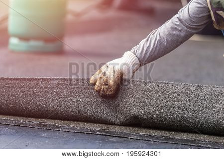 Group Of Worker Installing Tar Foil On The Rooftop Of Building. Waterproof System By Gas And Fire To
