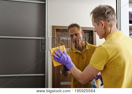 The man cleans the mirror in the house. He wipes the glass with the rag.