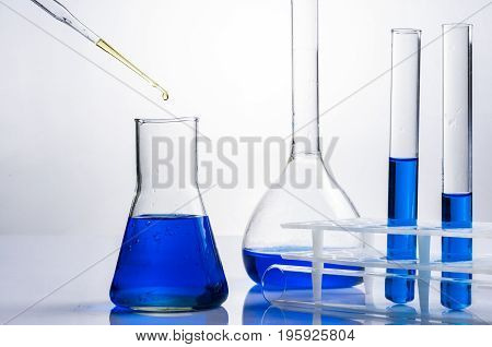 Science laboratory test tubes equipment filled with blue liquid.