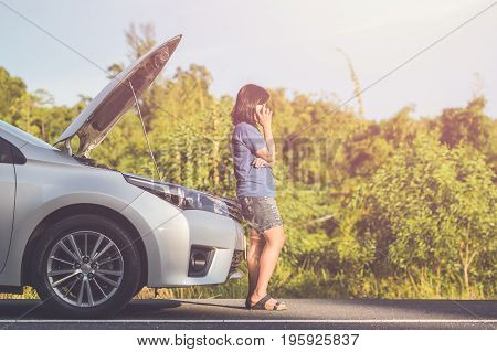 Woman Using Smartphone In Front Of Her Broken Car On The Road. Contacting Car Technician Or Need Hel
