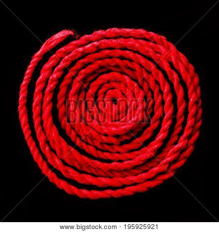Close -up red rope on black background.