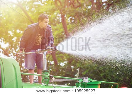PHUKET THAILAND - JUNE 20 : An unidentified people spraying water from the truck to landscape in the public park in Phuket on June 20 2017.