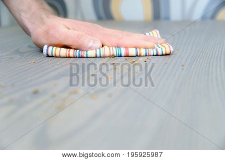 Man's hand with rag wipes the crumbs from the table.