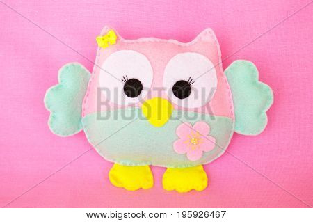 Funny felt owl toy on a pink fabric background
