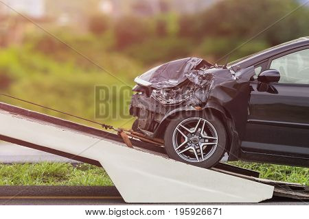 Black Car Get Damaged By Accident On The Road. And Moving To The Truck For Repair