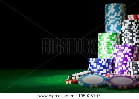 Stack of Poker chips on a green gaming poker table at the casino. Poker game concept. Playing a game with dice. Casino Concept for business risk chance good luck or gambling. chips for poker game