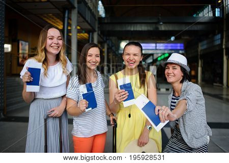 Charming tourists rejoice to the beginning of a travel. Girls sit at the station. They joyfully show the passports and tickets. Summer vacation. Anticipation of cheerful rest.