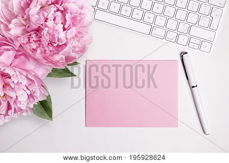 Female desktop with white keyboard and pink peonies top view mock up. Card for text or message