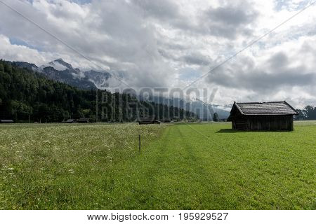 Old wooden hut on alpine meadows with mountains in background