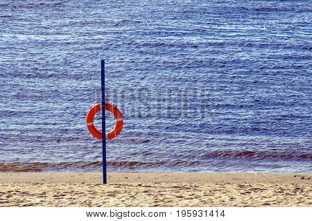 Red lifebuoy on sandy beach in hot summer evening.