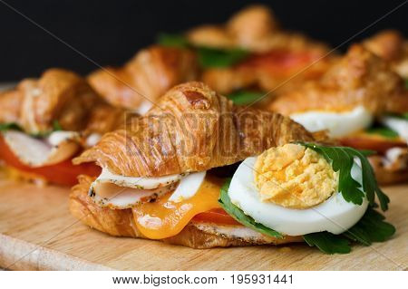 Croissant sandwich with egg parsley ham tomato and cheese on wooden background. Breakfast sandwiches