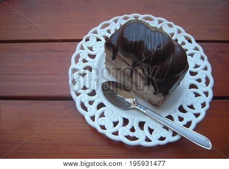 Chocolate cake on the white elegant plate with teaspoon on a wooden background.