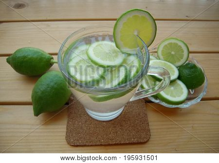 Lime water and sliced lime on a wooden table.