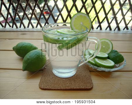 Lime water with sliced lime on veranda table.