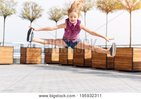 Active kid girl gymnast jumping on the street, doing splits. Stretching exercise, straight angle pose in the air. Young girl acrobat. The girl is engaged in gymnastics