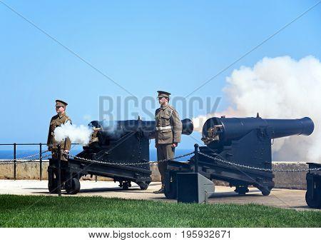 VALLETTA, MALTA - MARCH 30, 2017 - Soldiers firing cannons for the Noon Gun in Upper Barrakka Gardens Valletta Malta Europe, March 30, 2017.