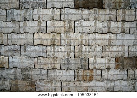 Interlocking wall with gray and brown concrete blocks. Concrete products Construction industry
