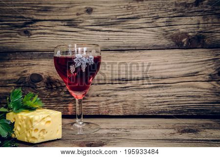 Beautiful picture with a glass of red wine yellow cheese and green herbs on wooden background with copy space