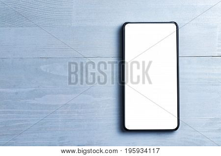 Bezel less smart phone with blank screen on a wooden background. Copy space on the left.