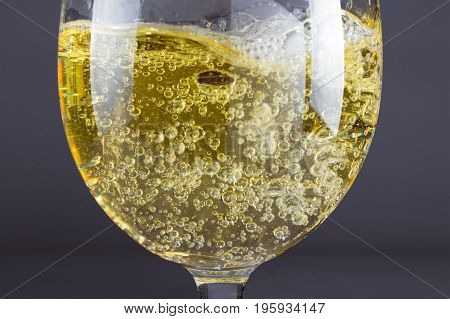 Pouring sparkling white wine into shiny glass against dark background.