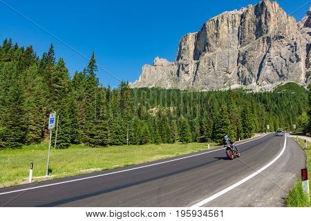 Wide angle view of mountain road with motorbike in Dolomites