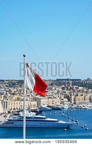 VALLETTA, MALTA - MARCH 30, 2017 - View towards Vittoriosa seen from Valletta with a Maltese flag in the foreground Valletta Malta Europe, March 30, 2017.