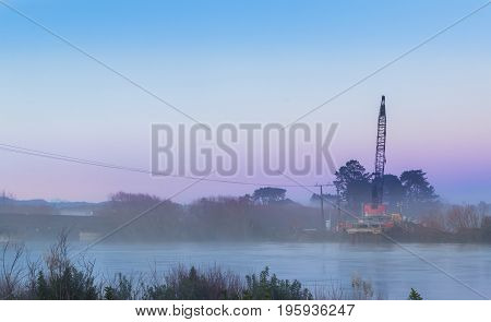 Early morning mist around a bridge building crane on the Manawatu river.