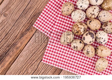 quail eggs on a red napkin on old wooden table. Top view.